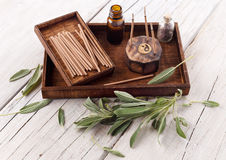Fresh sage leaves with spa aromatherapy kit. Sage leaves and wooden box with aromatherapy oils and incense sticks on wooden background stock photos