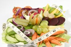 Fresh salad. Colourfull mixture of salad fruits & raw vegetables with imperial tape measure Royalty Free Stock Photos
