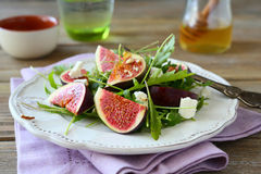 Fresh salad with arugula, figs, slices of cheese and honey Stock Photography