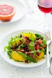 Fresh salad with arugula, orange, grapefruit, walnuts and pomegranate seeds on white table cloth Royalty Free Stock Photos