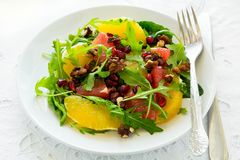 Fresh salad with arugula, orange, grapefruit, walnuts and pomegranate seeds on white table cloth Stock Photography