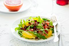 Fresh salad with arugula, orange, grapefruit, walnuts and pomegranate seeds on white table cloth Stock Images