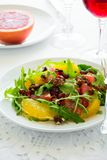 Fresh salad with arugula, orange, grapefruit, walnuts and pomegranate seeds on white table cloth Royalty Free Stock Photo