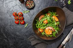 Fresh salad with arugula. Plate of fresh salad with arugula or salad rocket, shrimps, and tomato, top view. Healthy food concepts stock photo