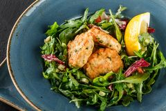 Fresh salad with arugula, spinach, avocado and vegetable cutlets with herbs, garnished with lemon in plate over dark background. Healthy vegan food, clean royalty free stock images