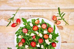 Fresh salad with arugula, strawberries, feta cheese and nuts. On wooden background. Vegetarian. Diet food. Italian food. Top view. Copy space stock image