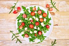 Fresh salad with arugula, strawberries, feta cheese and nuts. On wooden background. Vegetarian. Diet food. Italian food. Top view. Copy space stock photo