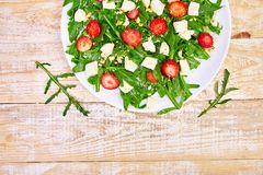 Fresh salad with arugula, strawberries, feta cheese and nuts. On wooden background. Vegetarian. Diet food. Italian food. Top view. Copy space royalty free stock image