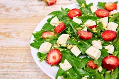 Fresh salad with arugula, strawberries, feta cheese and nuts. On wooden background. Vegetarian. Diet food. Italian food. Top view. Copy space stock photos