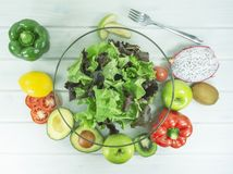 Fresh salad with avocado and fruits, fork on a wooden table stock photos