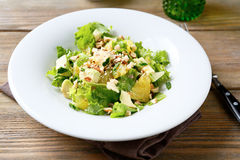 Fresh salad with avocado, orange and crushed nuts on a bowl Stock Images