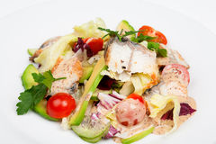 The fresh salad with avocado and smoked eel. On the plate. Close up view Stock Photo