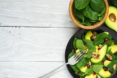 Fresh salad with avocado, spinach, pomegranate and walnuts in black plate with fork. healthy food. Top view with copy space Royalty Free Stock Images