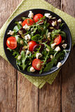 Fresh salad with beets, arugula, tomatoes, blue cheese and pumpk. In seeds close-up on the table. Vertical view from above Stock Image