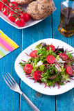 Fresh salad on blue wooden table Stock Photography