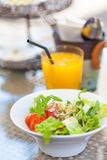 Fresh salad in a bowl served with orange juice Royalty Free Stock Photos