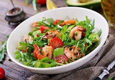 Fresh salad bowl with shrimp, tomato, avocado and arugula. On wooden background close up. Healthy food. Clean eating royalty free stock images
