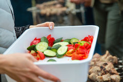 Fresh salad in box in hands outdoors Royalty Free Stock Image