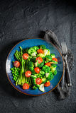 Fresh salad with broccoli, asparagus and cherry tomatoes. On black rock Stock Images