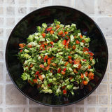 Fresh salad with broccoli, red pepper, fennel, raisins, sunflower seeds. In a black plate Stock Image