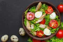 Fresh salad caesar with chicken, quail eggs, tomatoes and lettuce in a bowl Royalty Free Stock Photos