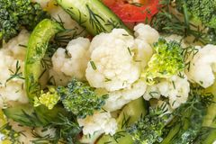 Fresh salad of cauliflower with cucumber, broccoli and greens, olives and sweet pepper in a glass bowl on a white background. Close-up Stock Photography