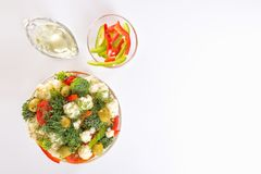 Fresh salad of cauliflower with tomato, broccoli, greens, olives and sweet pepper in a glass bowl along with a glass nipple. On a white background. Top view Stock Image