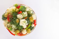 Fresh salad of cauliflower with tomato, broccoli, greens, olives and sweet pepper in a glass bowl on a white background. Top view. Copy space Royalty Free Stock Photos