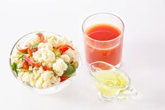Fresh salad of cauliflower with tomato, broccoli, olives, sweet pepper, greens with a glass of tomato juice. And a glass nipple on a white background Royalty Free Stock Photo