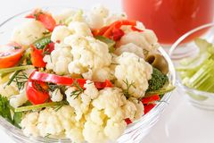Fresh salad of cauliflower with tomato, broccoli, olives, sweet pepper, herbs, celery and a glass of tomato juice. On white background. Close-up Stock Photography