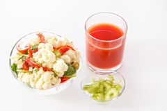 Fresh salad of cauliflower with tomato, broccoli, olives, sweet pepper, herbs, celery and a glass of tomato juice. On white background Royalty Free Stock Images