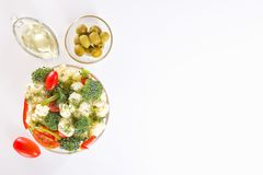 Fresh salad of cauliflower with tomato, vegetables, broccoli, greens and olives in a glass bowl. With a glass nipple on a white background. Top view. Copy space Stock Photos