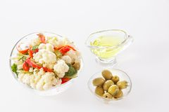 Fresh salad of cauliflower with tomato, vegetables, broccoli, greens and olives in a glass bowl with a glass nipple. On a white background Royalty Free Stock Photos