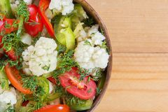 Fresh salad of cauliflower with tomatoes, broccoli, olives, sweet pepper, herbs and vegetables in a bowl on a wooden table. Top view. Copy space. Close-up Stock Image