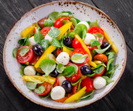 Fresh salad with cheese. On a dark wooden table. Flat lay Royalty Free Stock Photo