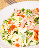 Fresh salad with cheese, ham and vegetables. On plate Stock Images
