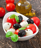 Fresh salad with cherry tomatoes, basil, mozzarella. And black olives Stock Photography