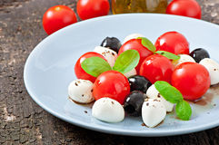 Fresh salad with cherry tomatoes, basil, mozzarella. And black olives Royalty Free Stock Photography