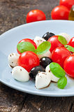 Fresh salad with cherry tomatoes, basil, mozzarella. And black olives Stock Images