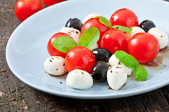 Fresh salad with cherry tomatoes, basil, mozzarella. And black olives Royalty Free Stock Photos