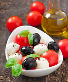 Fresh salad with cherry tomatoes, basil, mozzarella. And black olives Royalty Free Stock Images