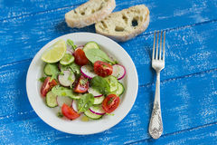 Fresh salad with cherry tomatoes, cucumber, radish and spinach on a white plate. On blue wooden background Royalty Free Stock Images
