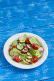 Fresh salad with cherry tomatoes, cucumber, radish and spinach on a white plate. On blue wooden background Stock Images