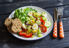 Fresh salad with cherry tomatoes, cucumbers, sweet peppers, celery and quail eggs. Royalty Free Stock Image