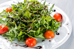 Fresh salad of cherry tomatoes, lettuce, beniseed and sauce on a white plate close up Royalty Free Stock Image