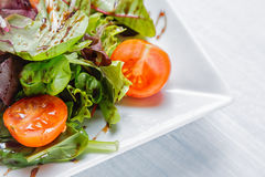 Fresh salad of cherry tomatoes, lettuce and sauce on a white plate close up Royalty Free Stock Photos