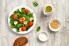 Fresh salad with cherry tomatoes, mozzarella and spinach. On a white wooden surface Stock Photography