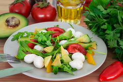 Fresh salad with cherry tomatoes, rucola, mozzarella and bulgarian pepper. Wooden background. Top view. Close-up Royalty Free Stock Photos