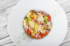 Fresh salad with chicken breast, artichokes, cherry tomatoes, lettuce and cheese parmesan on wooden background close up Stock Image