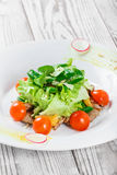 Fresh salad with chicken breast, baby spinach, lettuce, cherry tomatoes and cheese on wooden background Stock Image